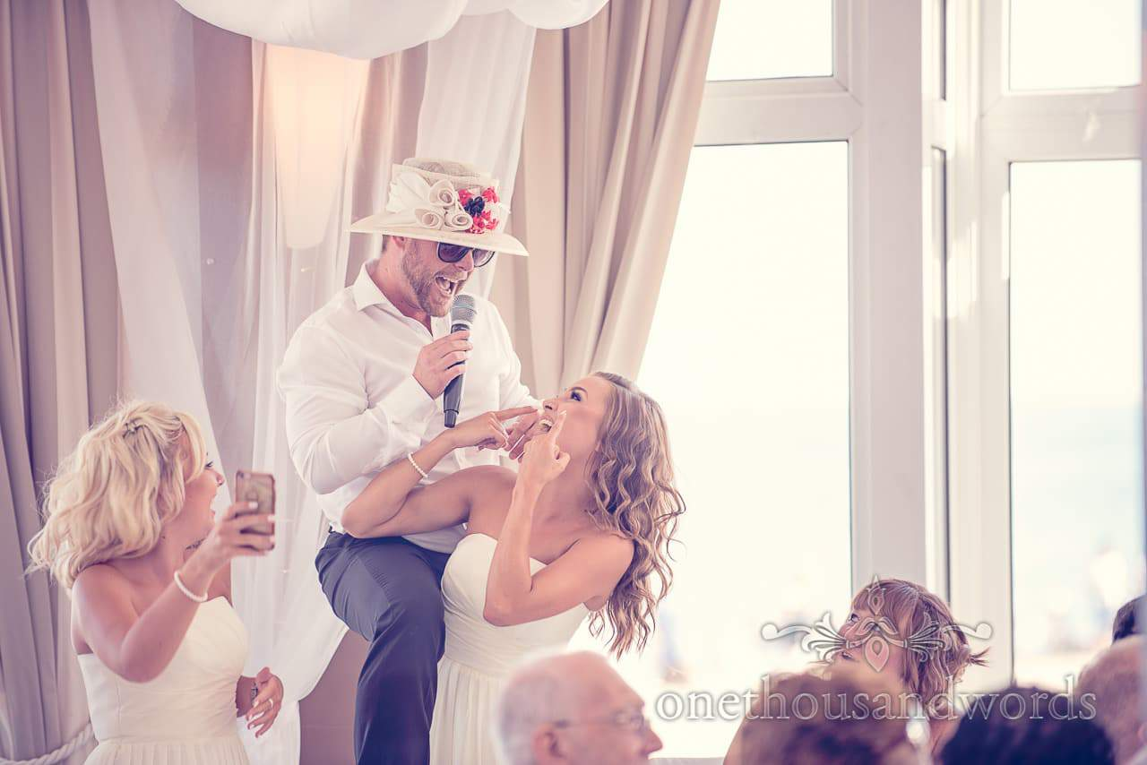 Silver service singing waiter singing with bridesmaid in wedding guests floral hat