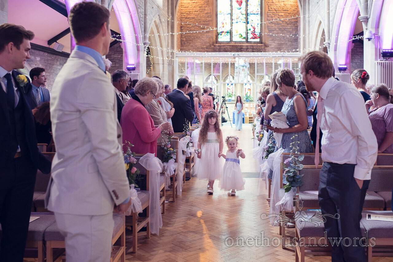 Small flower girls walk down church aisle at christian wedding service in Poole