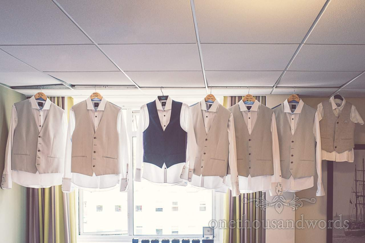 Tan wedding waistcoats and white shirts hanging in window on wedding morning