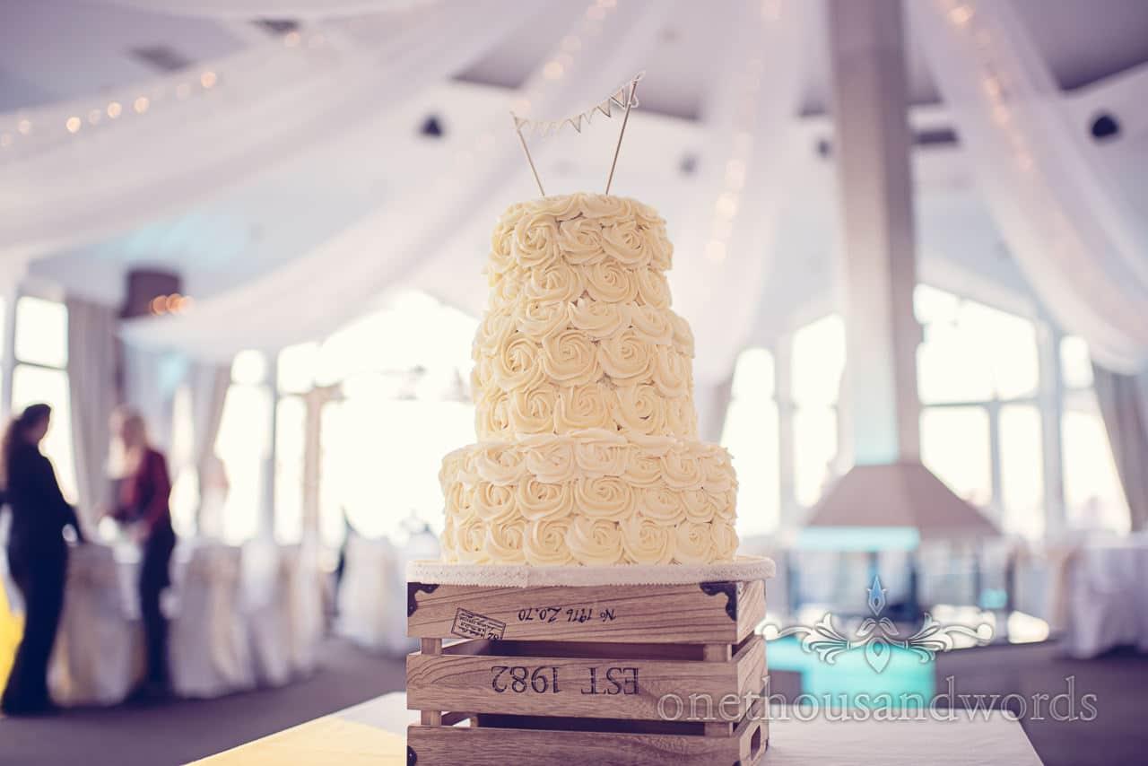 Three tier cream coloured wedding cake with icing flower swirls in Sandbanks Hotel, Poole