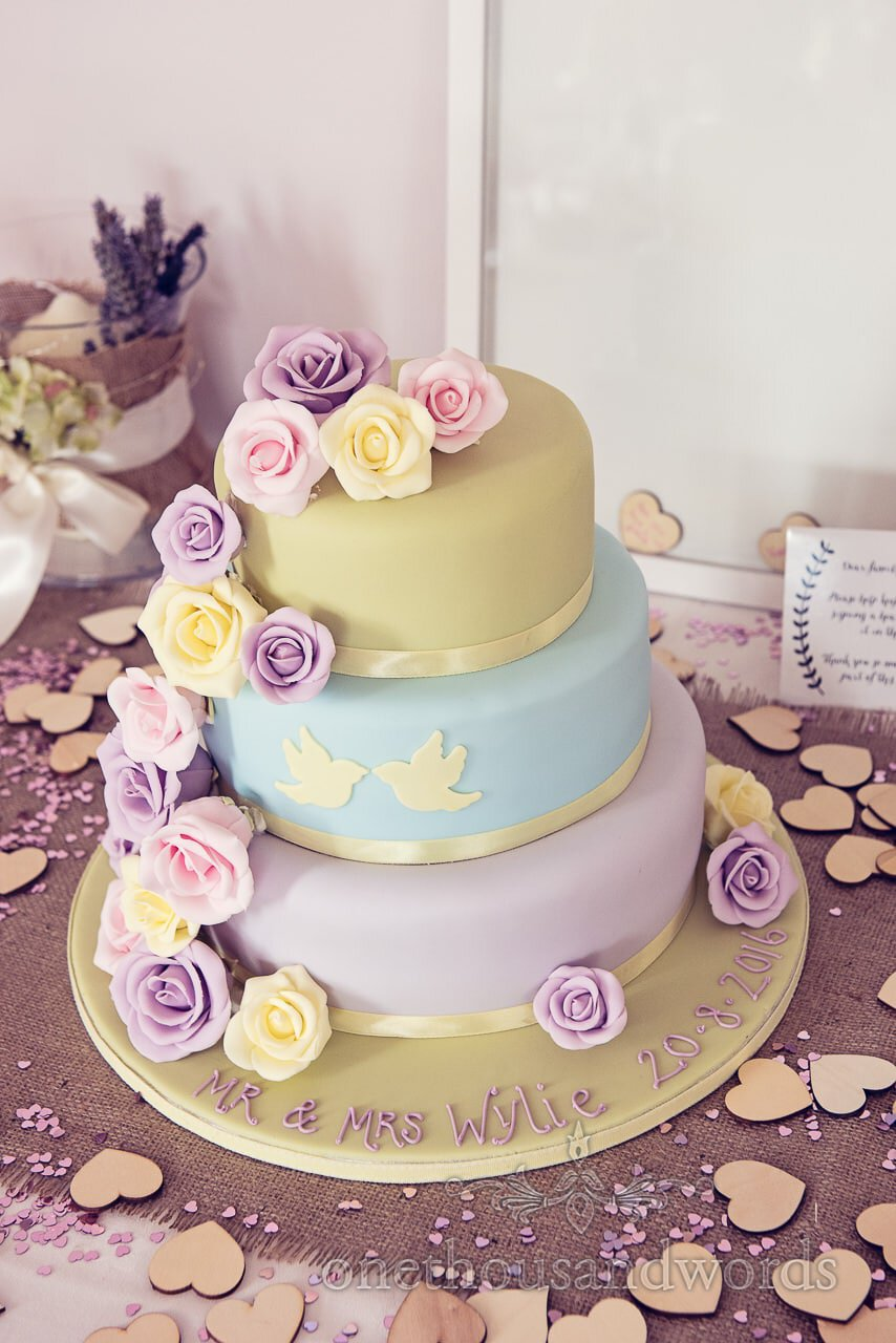 Three tier multi coloured pastel wedding cake with love birds and flowers