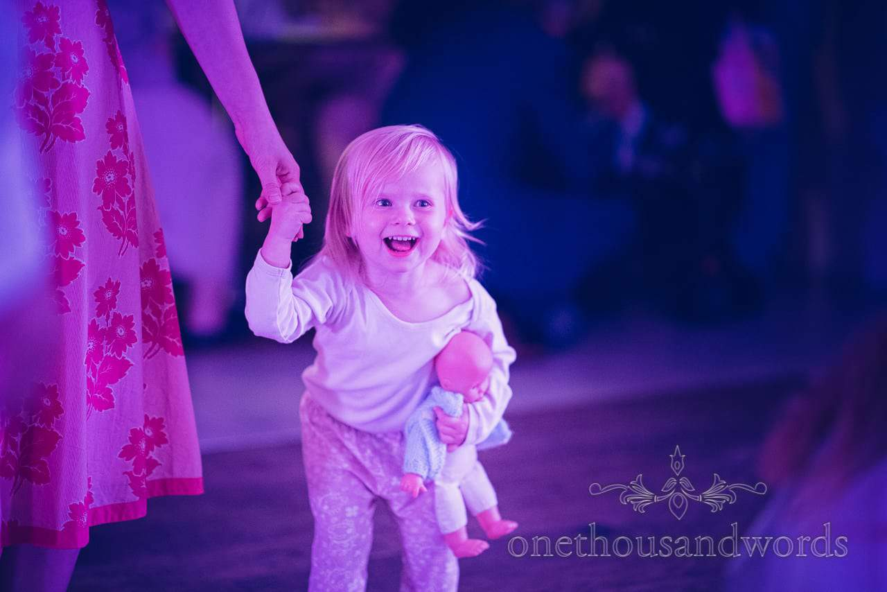 Toddler with doll laughing on the dancefloor at the Italian Villa wedding