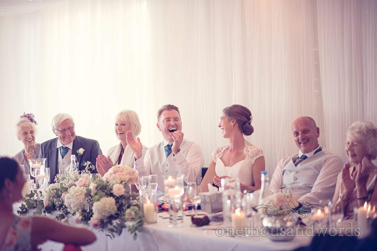 Top table laugh together during best mans speech at harbour heights wedding
