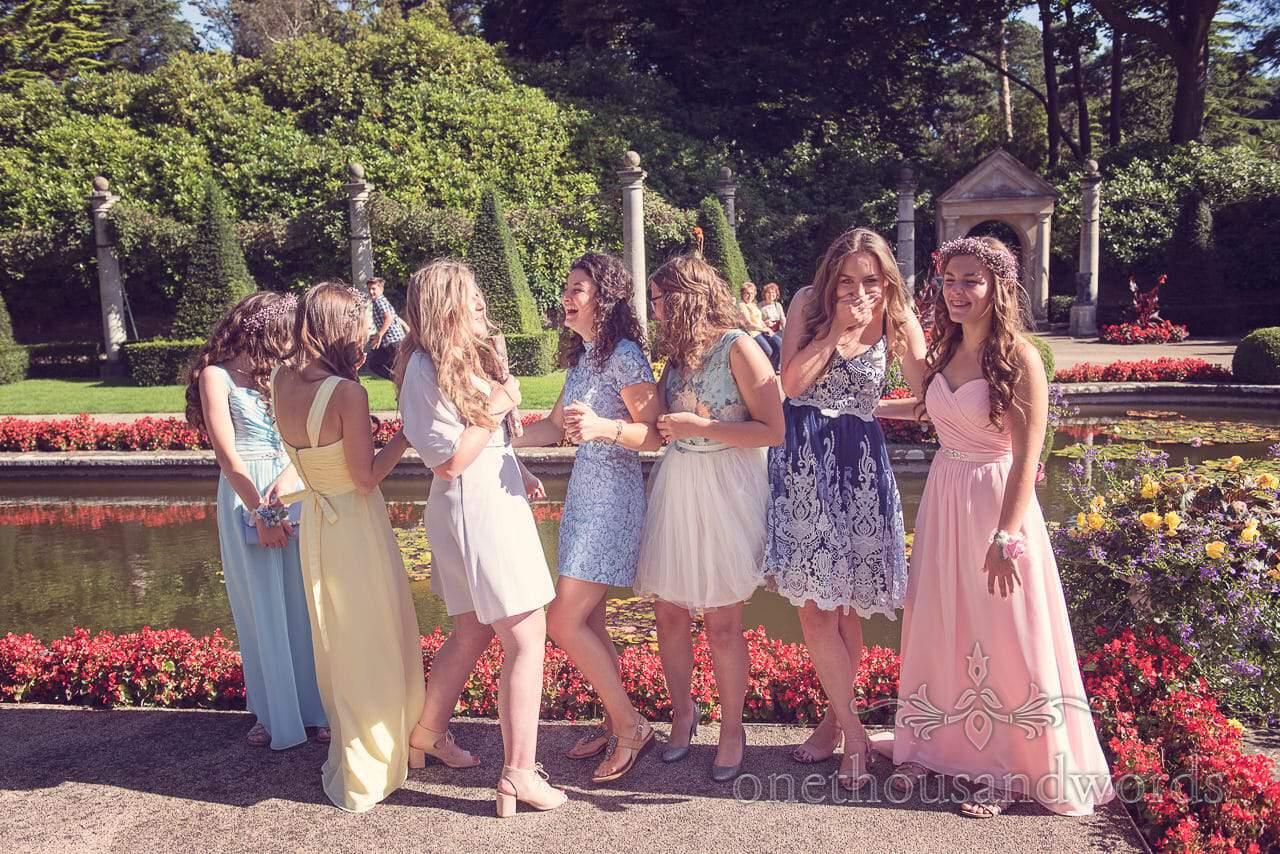 weddign guests lauging in Italian gardens during Italian Villa wedding photographs