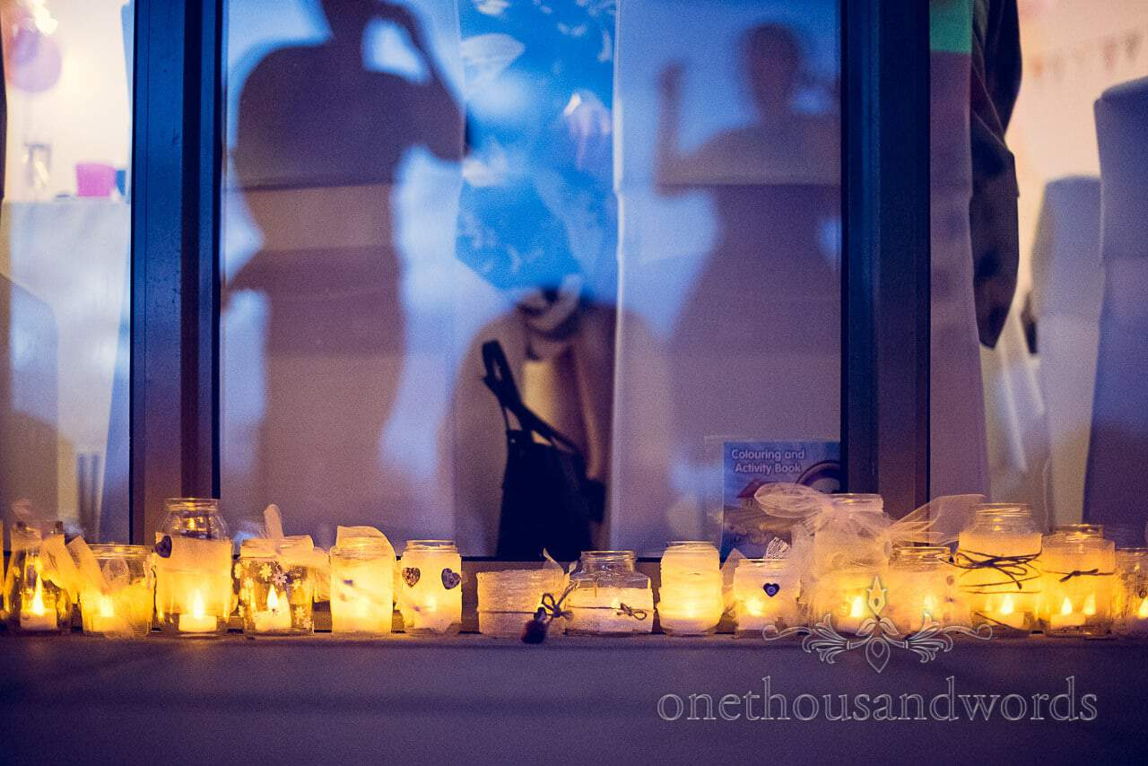 Wedding candles in jars with love hearts, lace and string outside wedding venue