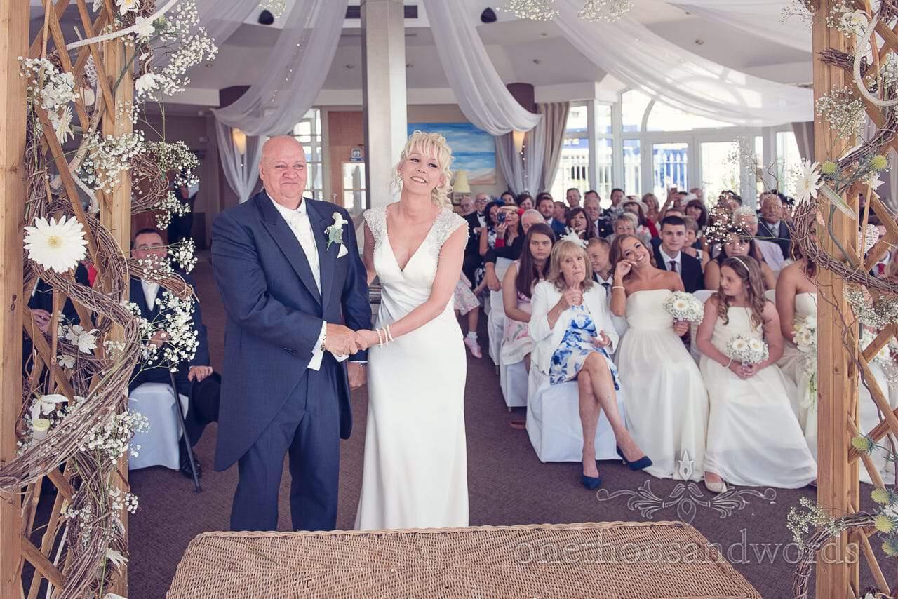 Wedding ceremony under floral arbour at Sandbanks Hotel Wedding