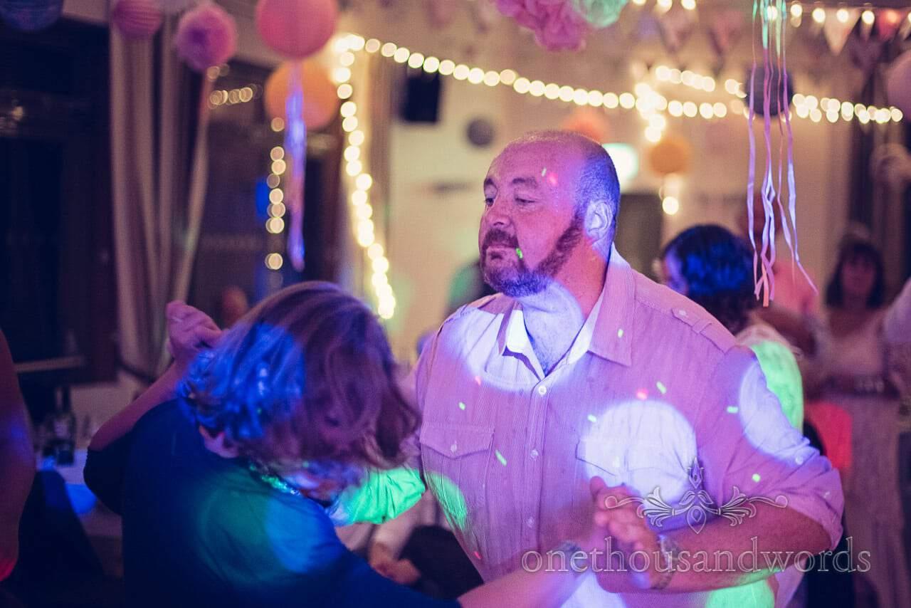 Wedding guest dancing under multi coloured disco lighting
