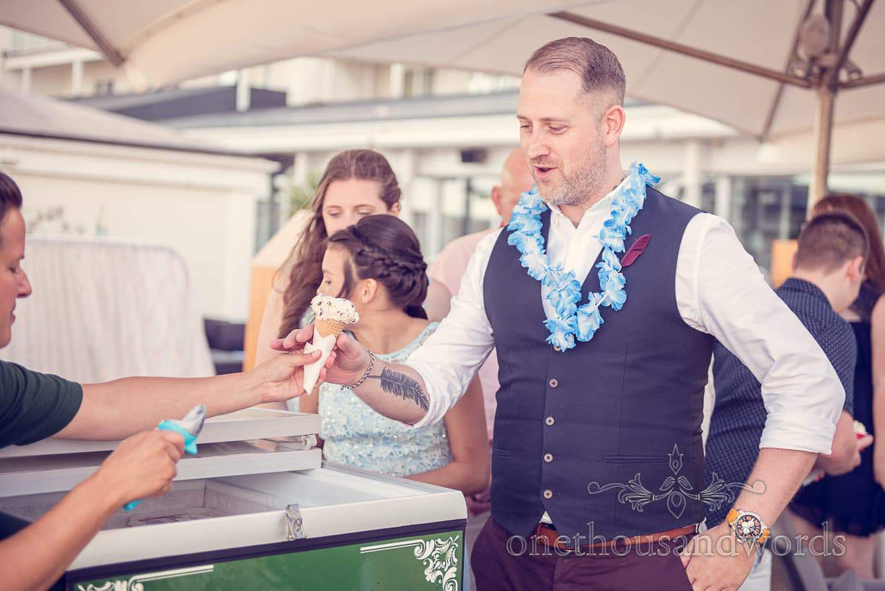 Wedding guest enjoys ice cream at Sandbanks Hotel wedding venue by the sea