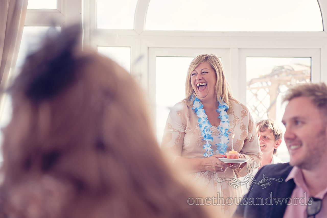 wedding guest in Hawaiian lei holds birthday cake at seaside theme wedding photographs