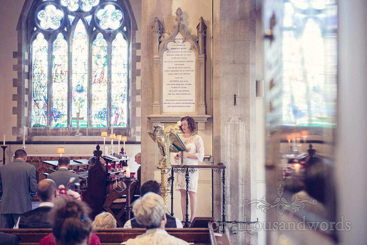 Wedding guest in pulpit conducting a reading during church wedding ceremony in Swanage