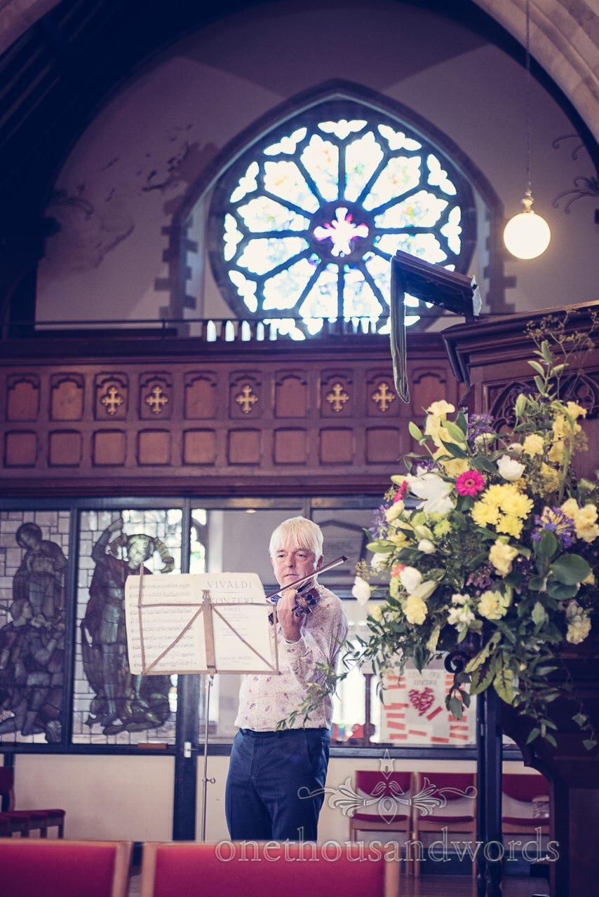 Wedding guest plays violin at Swanage church wedding ceremony