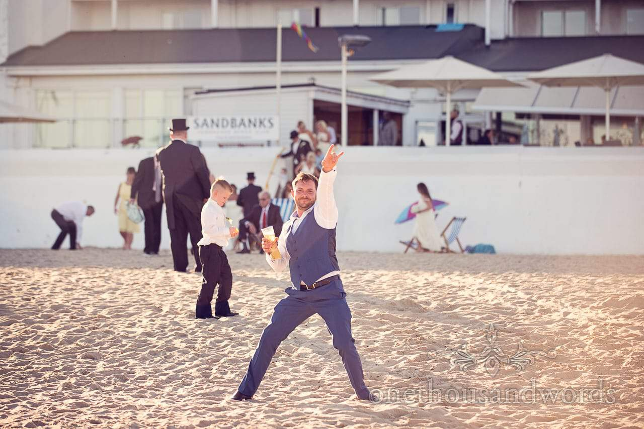 Wedding guest poses in sun on Sandbanks Beach Hotel Wedding