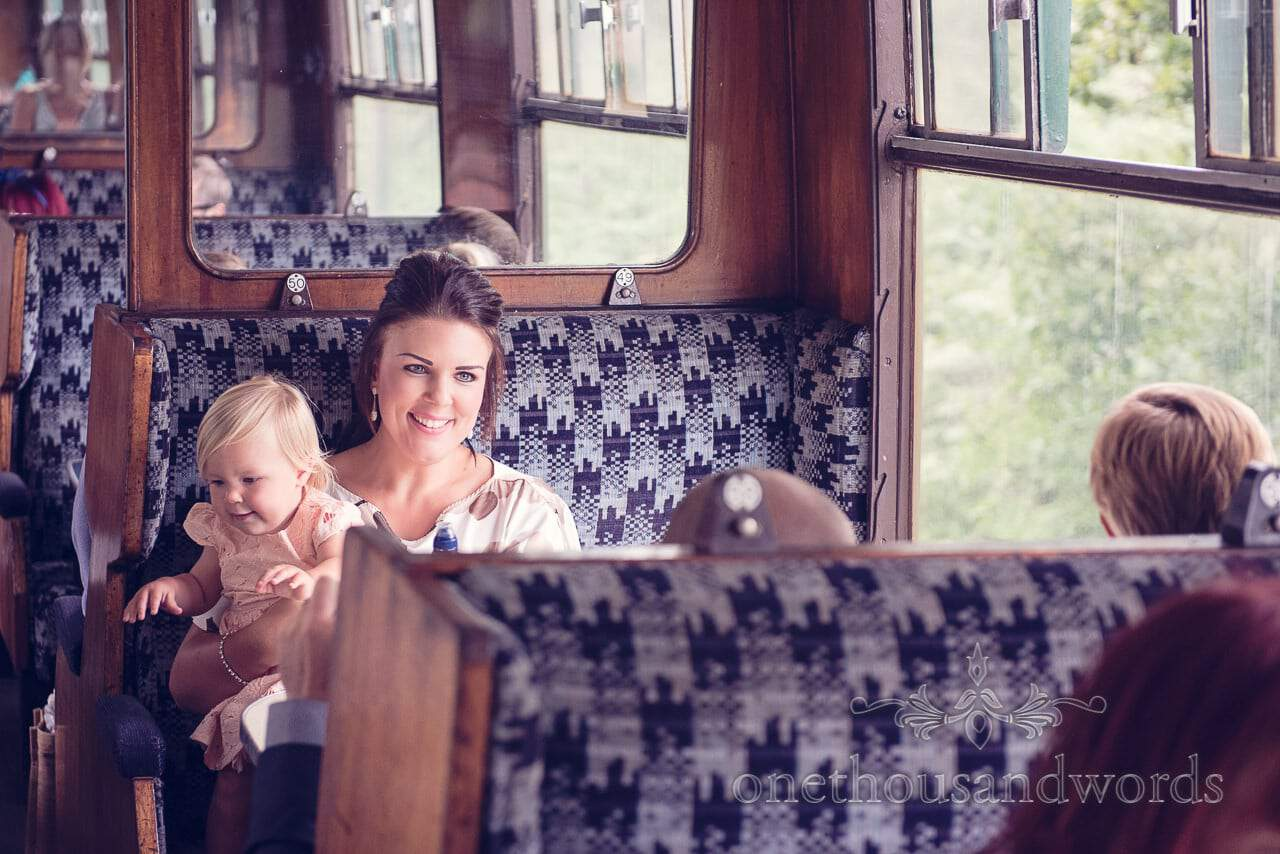 Wedding guest with baby on Swanage steam railway train carriage