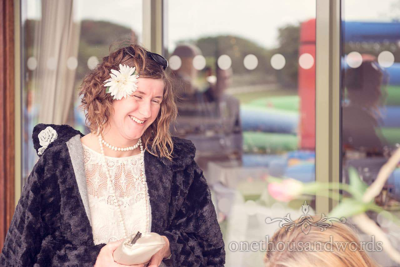 Wedding guest with fur coat and flower in her hair at Harmans Cross Wedding