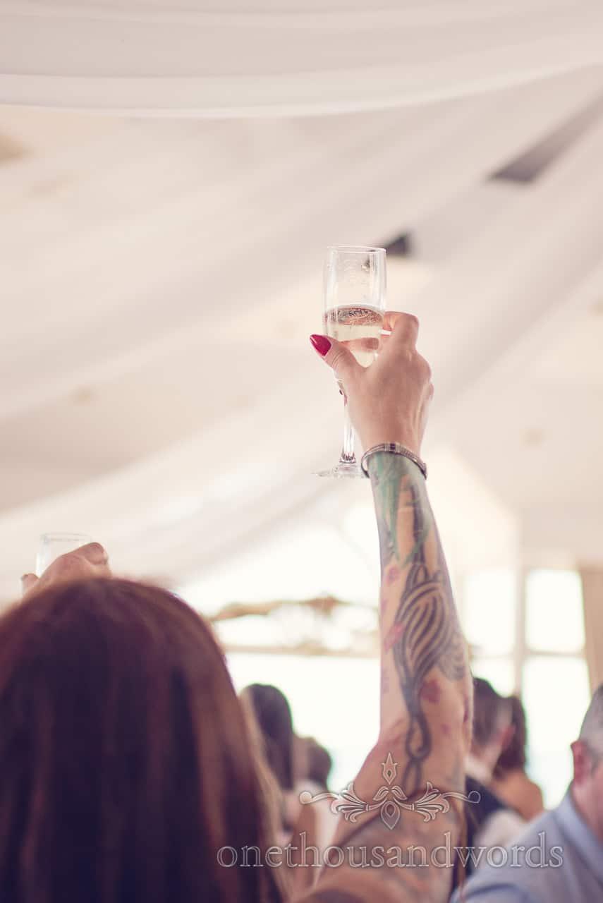 Wedding guest with tattoos toasts wedding speeches at Sandbanks Hotel Wedding