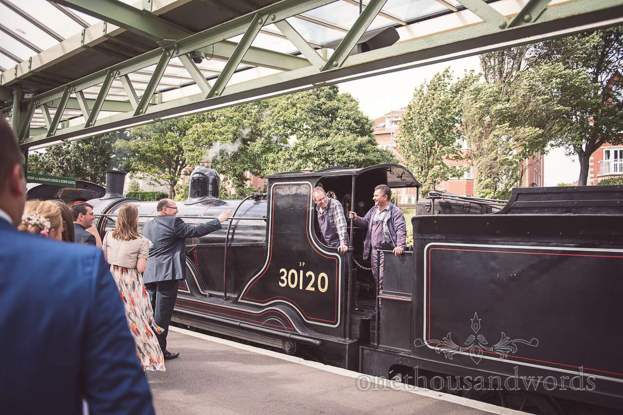 Wedding guests at Swanage steam railway station wave to steam train driver