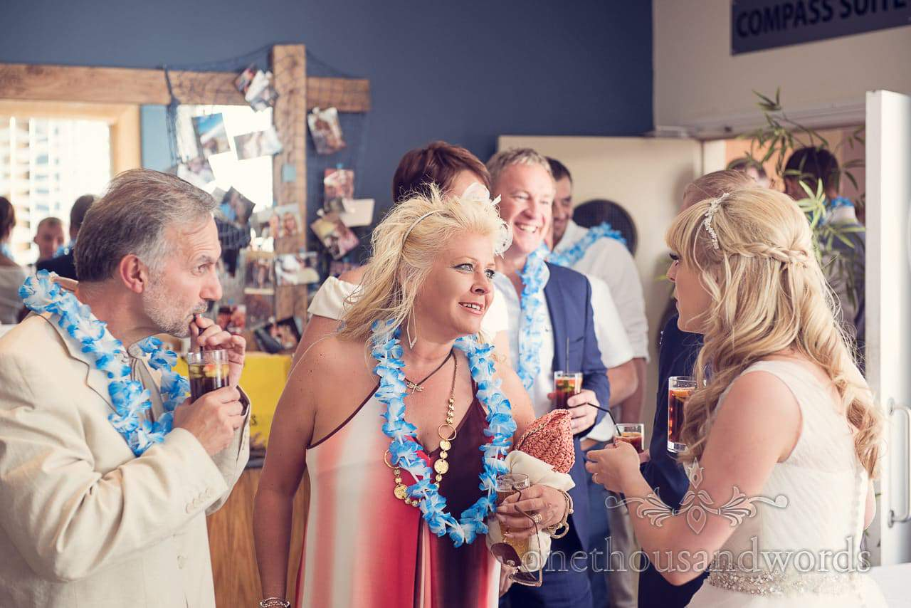 wedding guests in blue and white leis at seaside theme wedding in Dorset