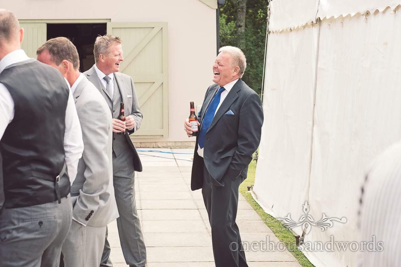 Wedding guests laughing and enjoying a beer at Harmans Cross Village Hall Wedding