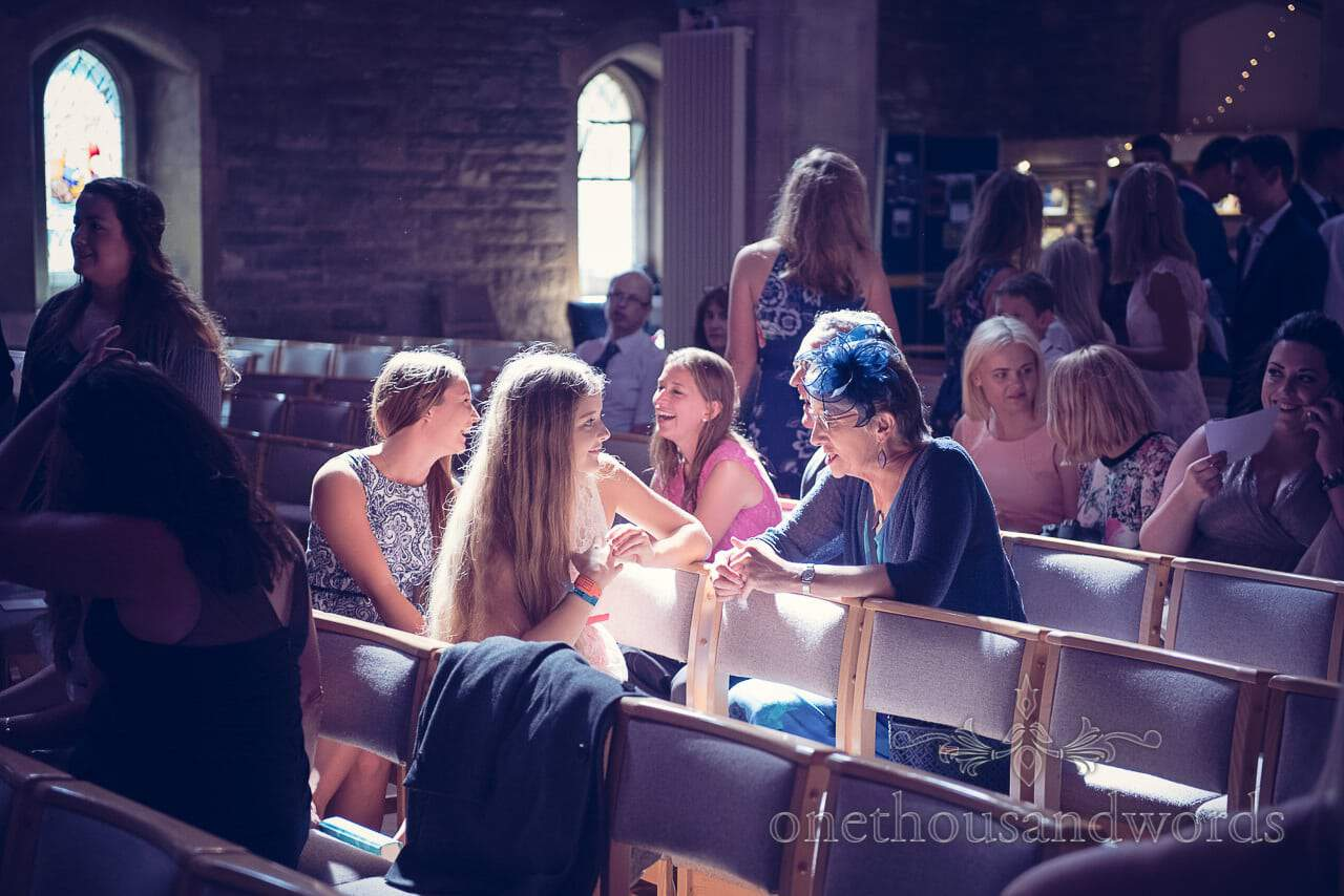 wedding guests laughing in shaft of light at St Marys Longfleet church before wedding
