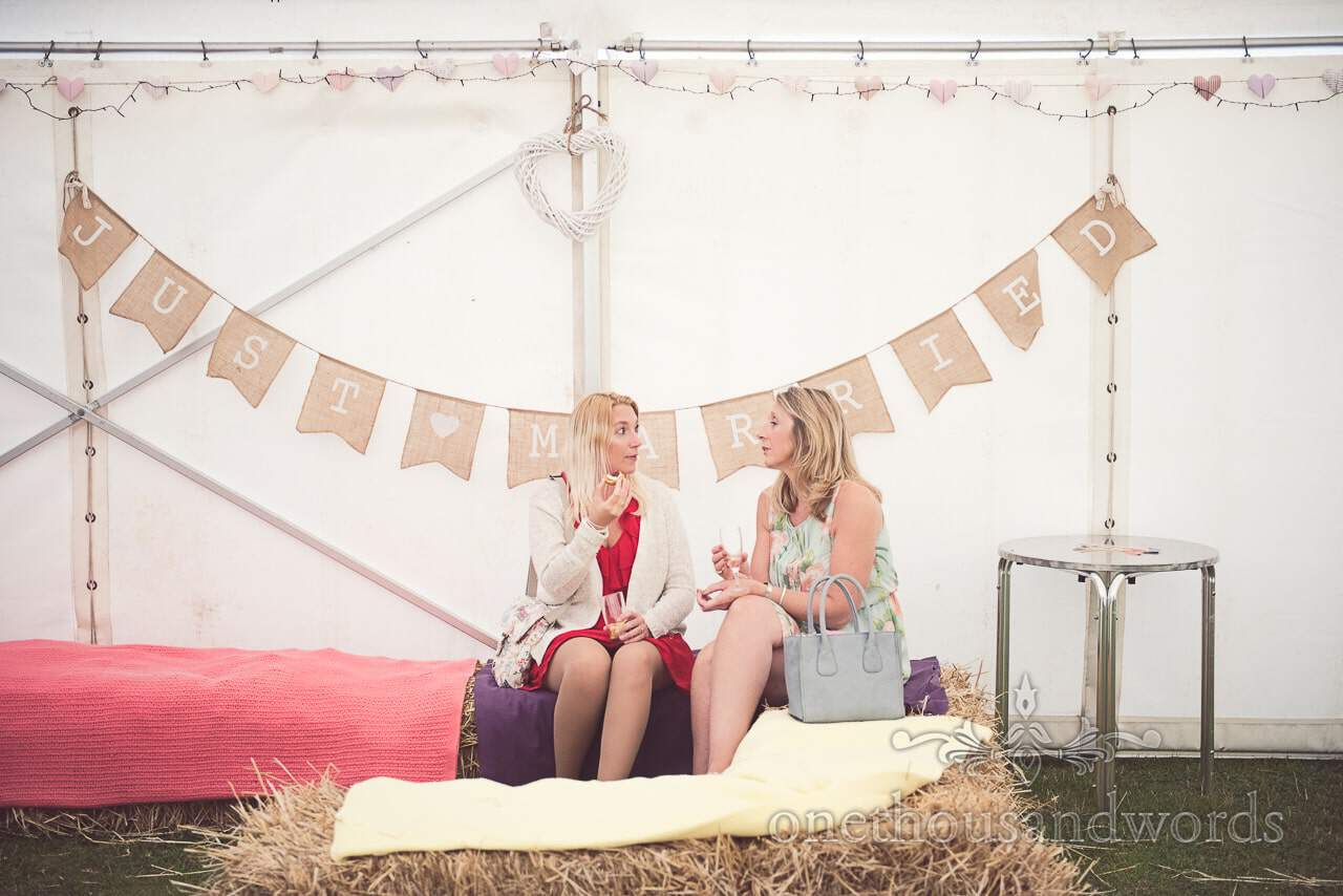Wedding guests sit on staw bales in wedding marquee under just married bunting