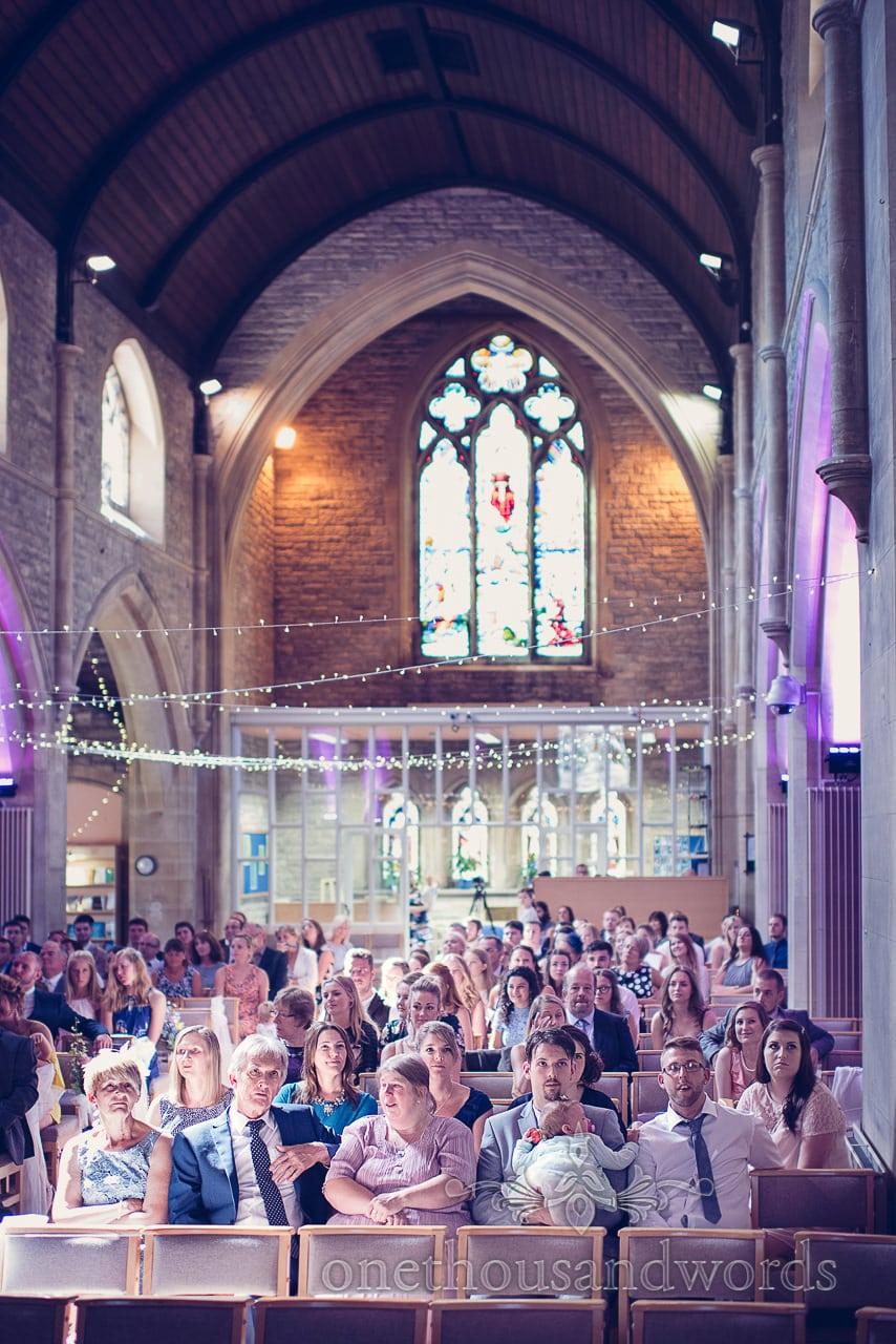 Wedding guests under fairly lights with purple lighting at St Marys Longfleet Church wedding