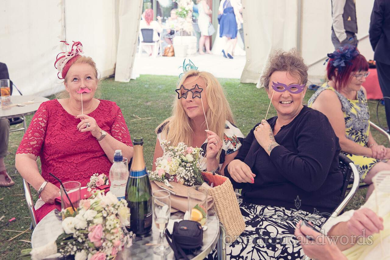 Wedding guests with glasses and moustaches on sticks