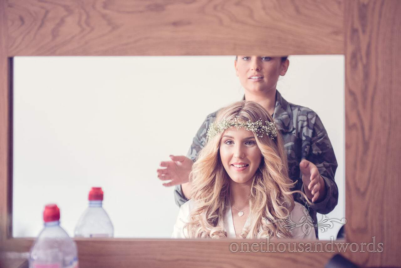 Wedding hair dresser with beautiful blonde bride in floral headband