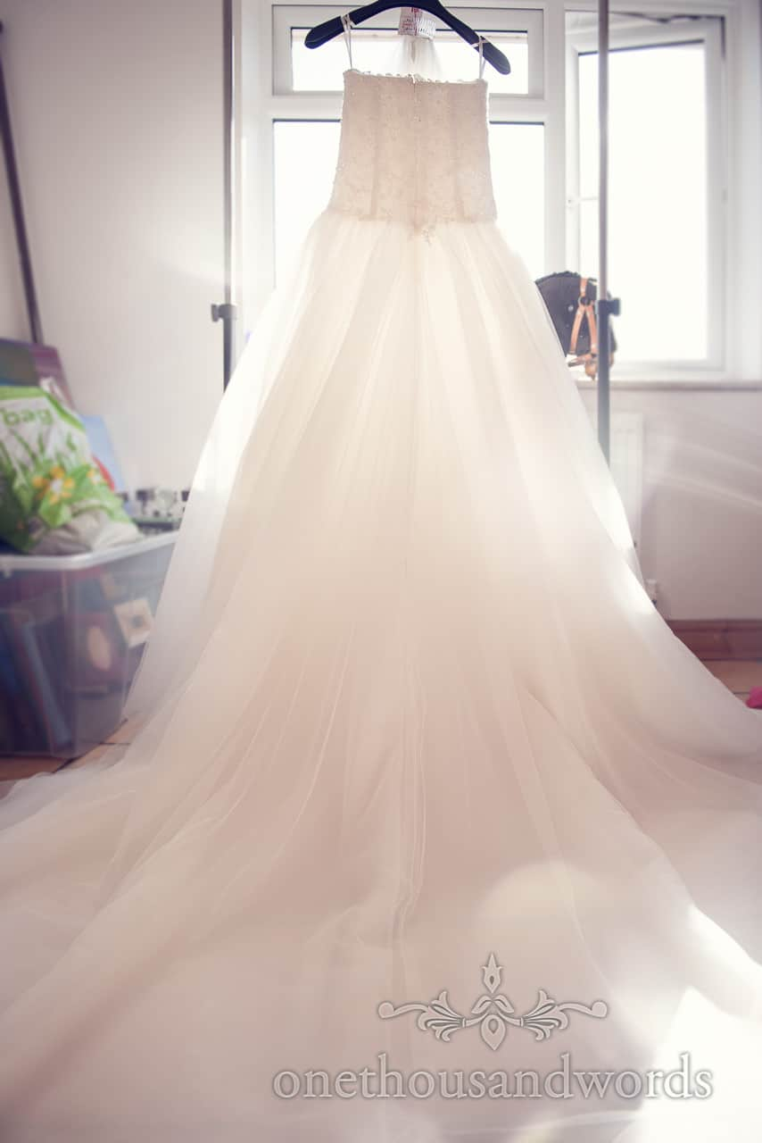 White wedding dress hanging in window with hobby horse