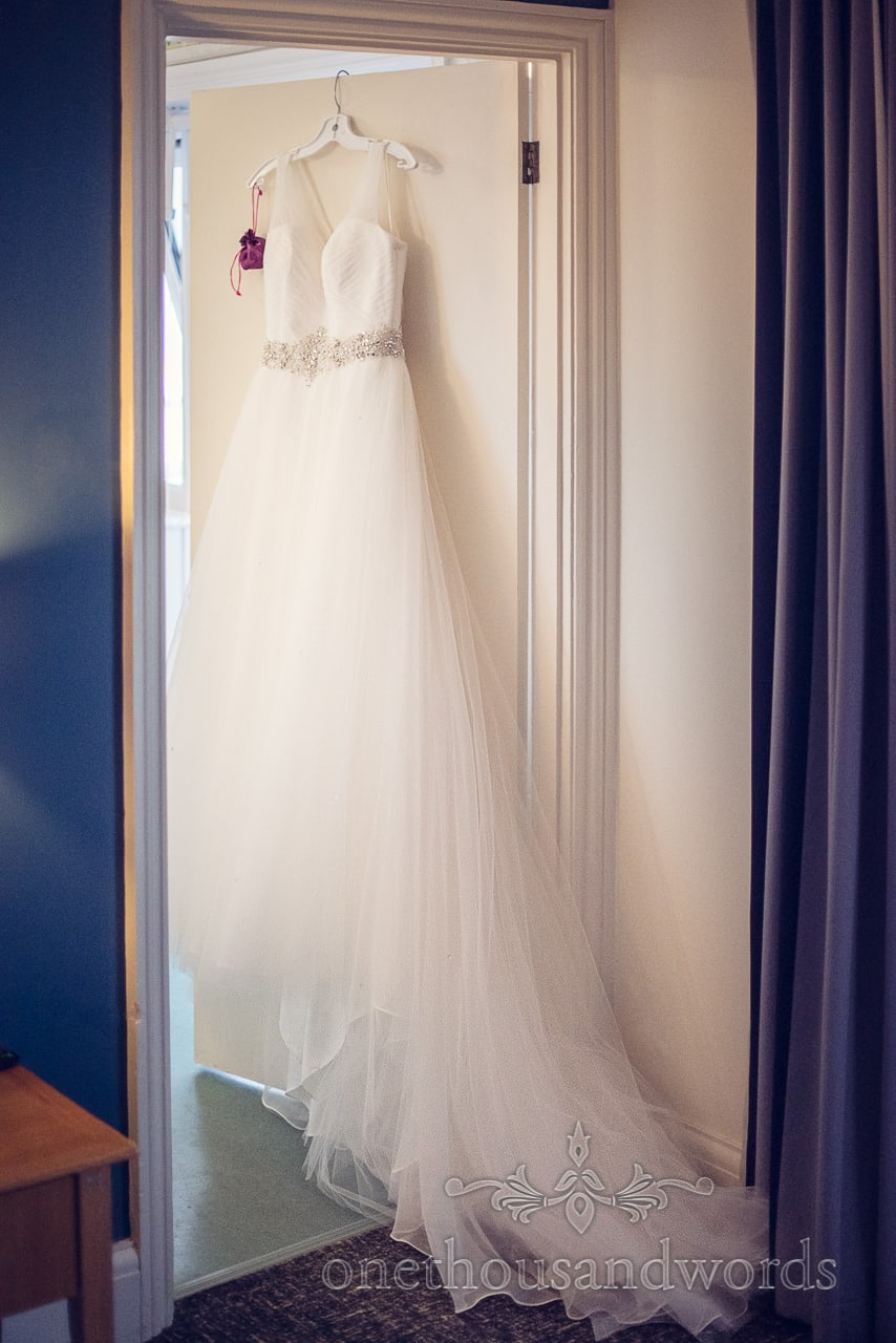 White wedding dress hanging on door on wedding morning at Sandbanks Hotel in Dorset
