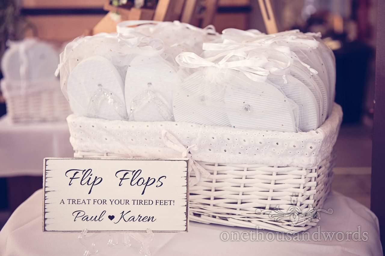 White Wicker basket of white wedding flip flops at Sandbanks Hotel Wedding