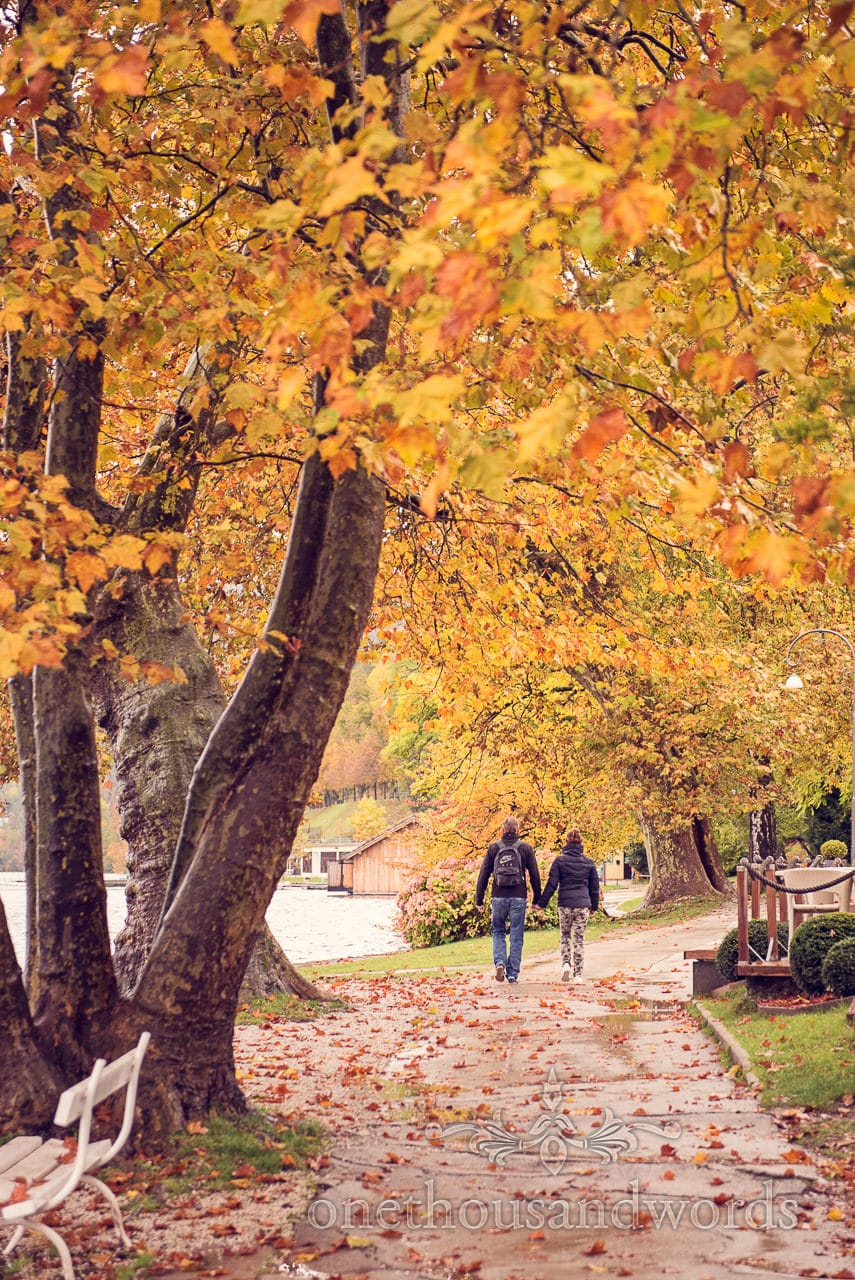 Autumn leaves with bride and groom walking around lake bled, Slovenia