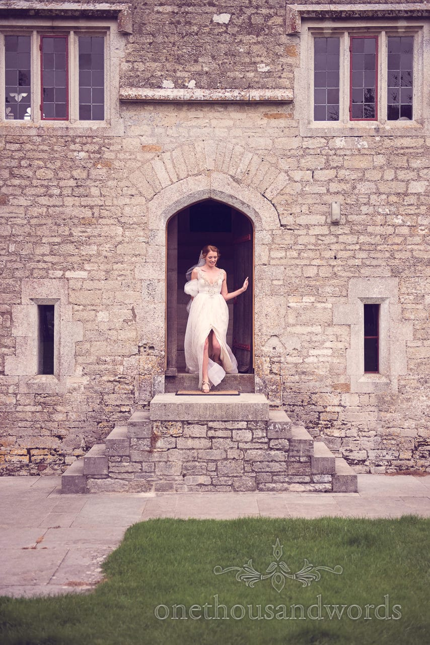 Beautiful bride in gorgous wedding dress steps out of Woodsford castle on wedding morning