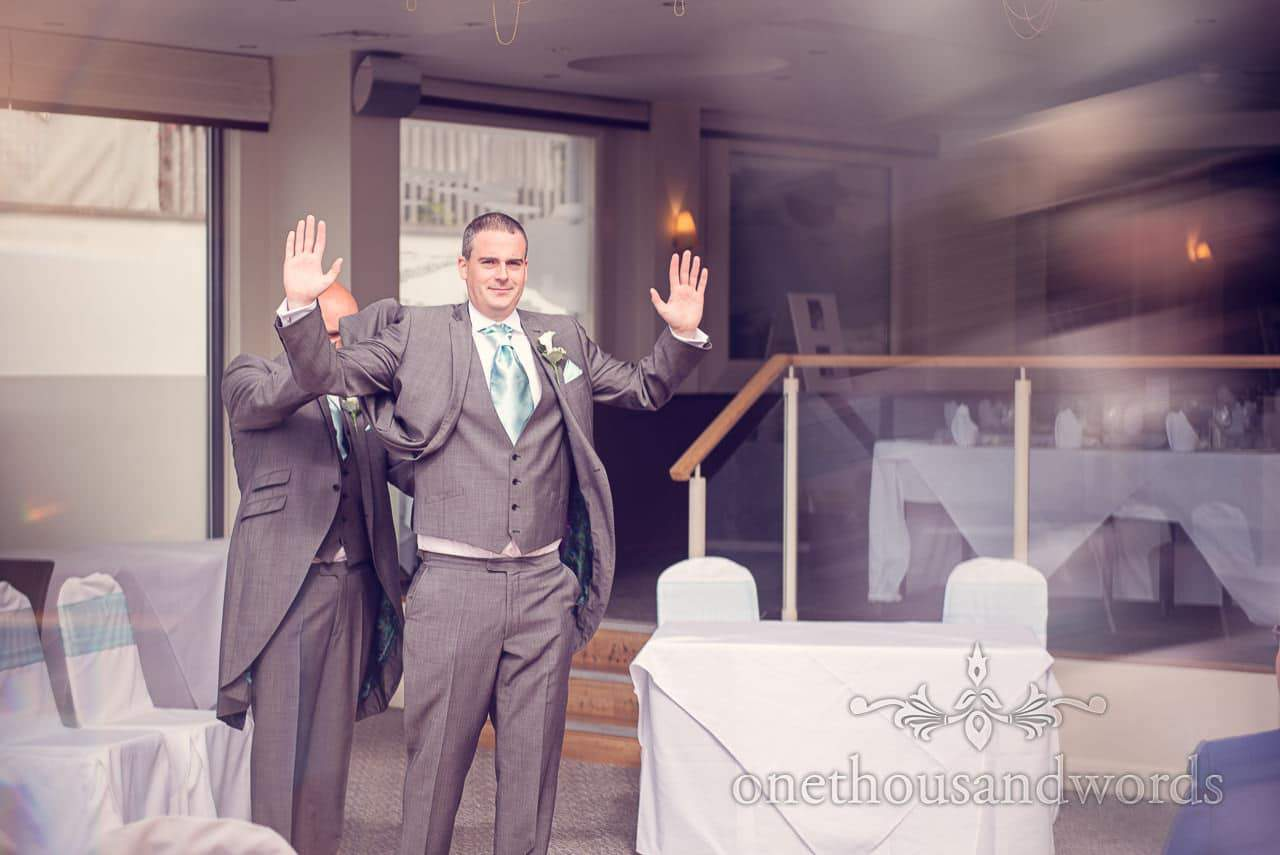Best man ajdusts groom waistcoat at Harbour Heights Hotel outdoor wedding