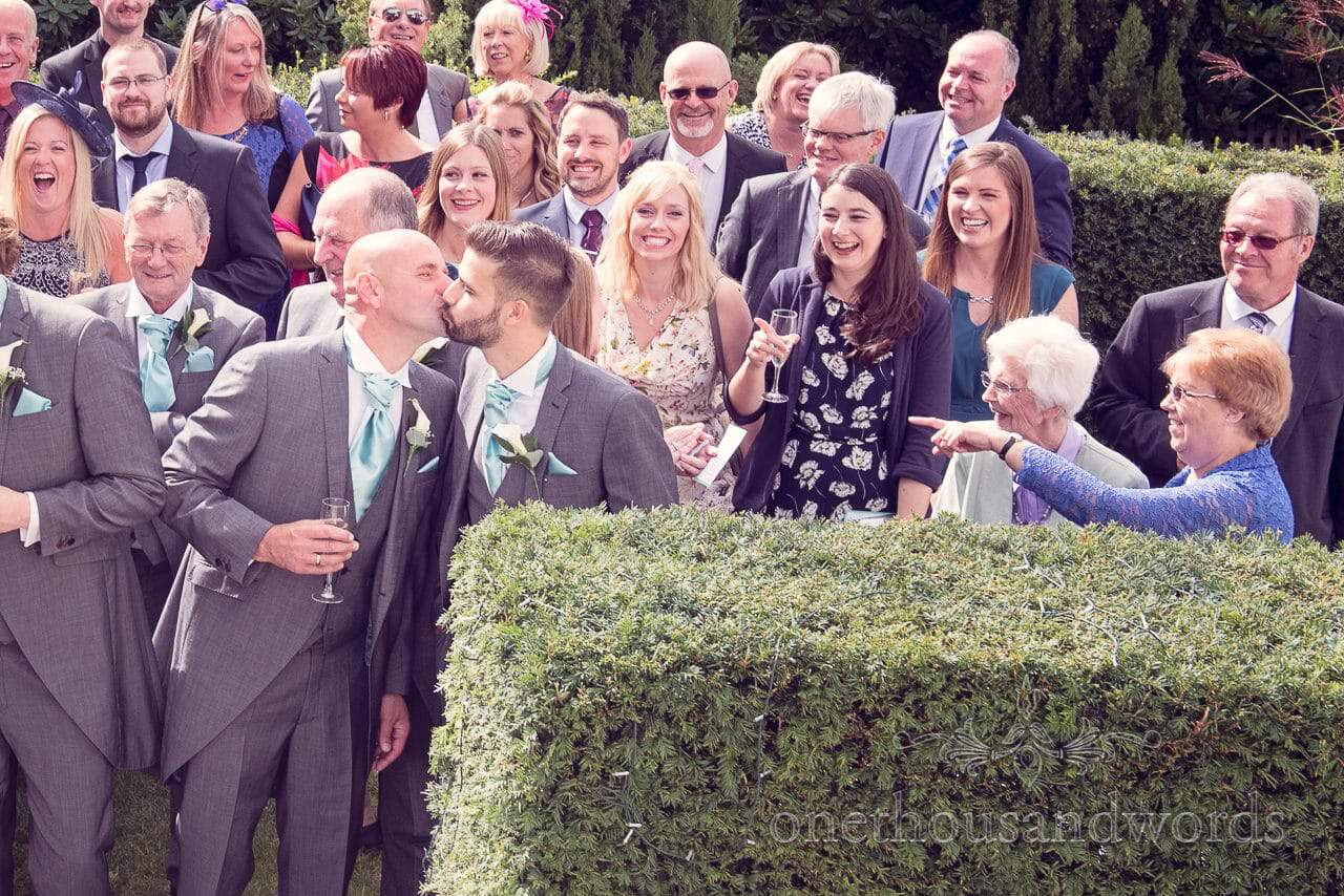 Best man and usher kiss during group photographs at Harbour Heights Hotel outdoor wedding