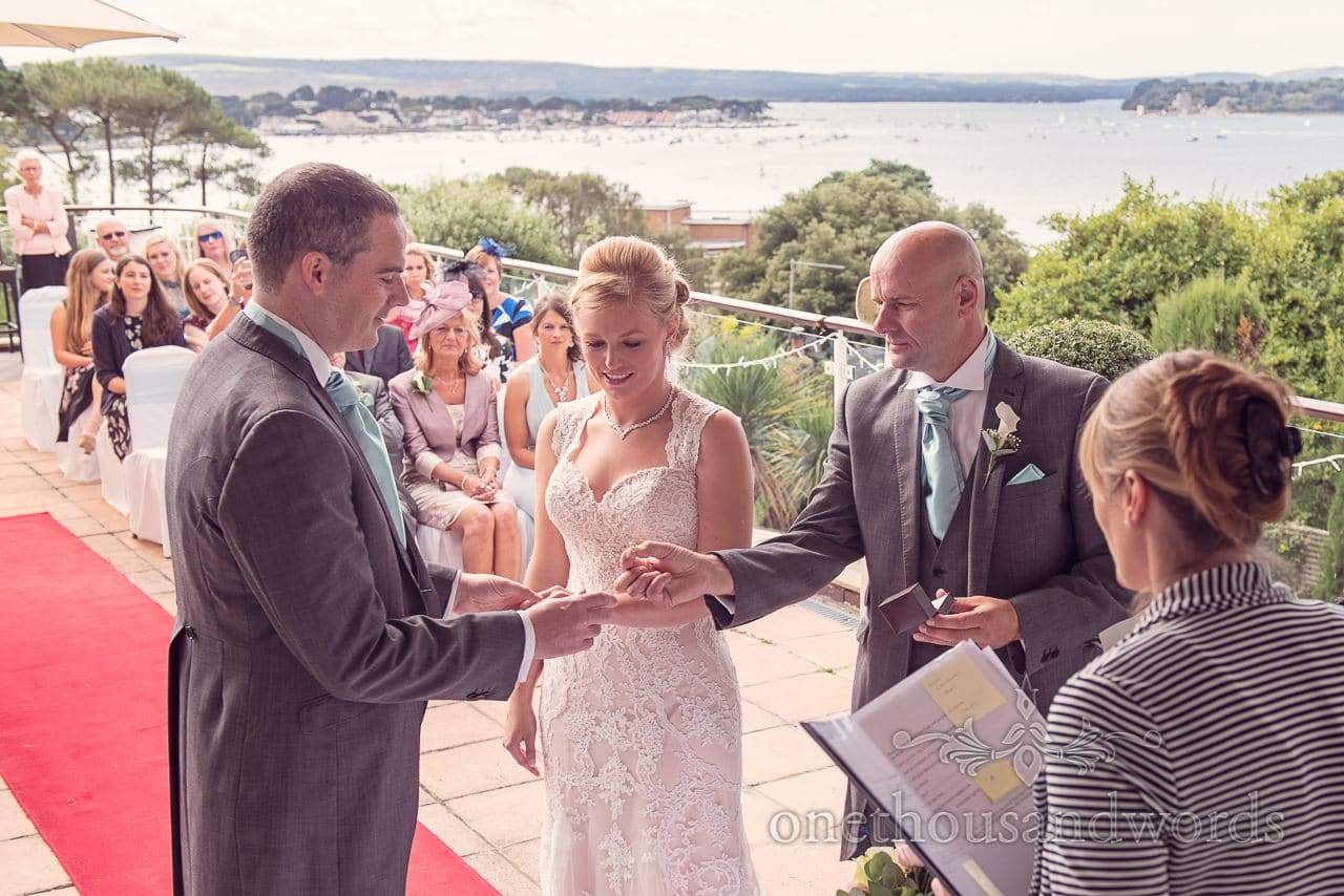 Best man hands groom brides ring at Harbour Heights Hotel outdoor wedding