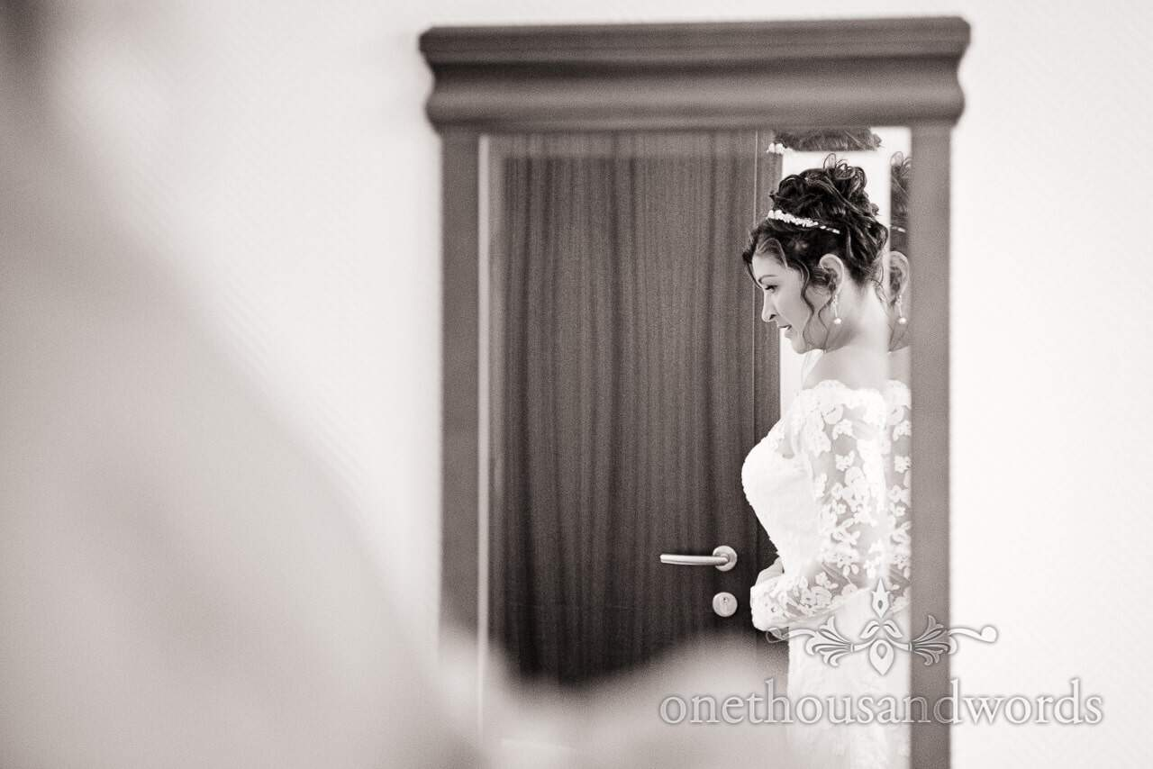 Black and white portrait photograph of bride in mirror on wedding morning in Bled