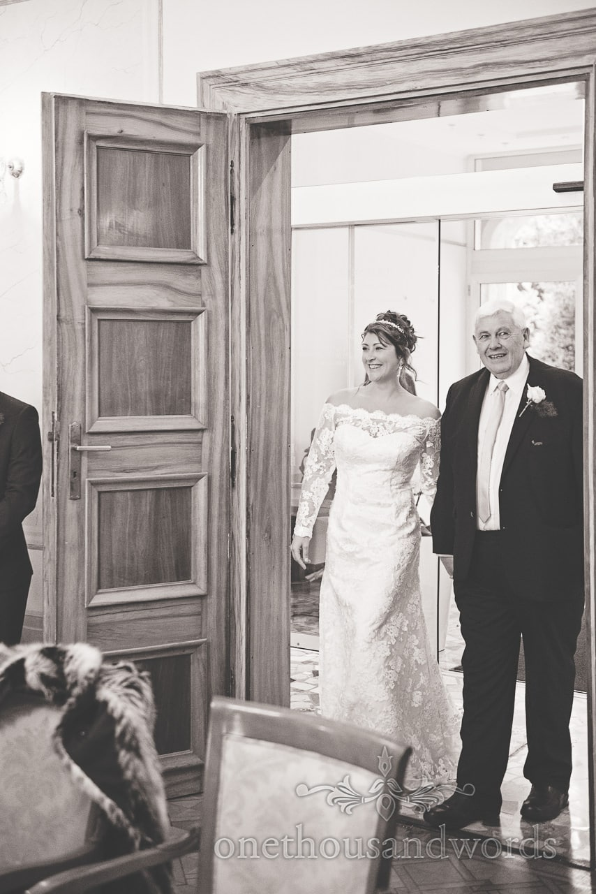 Black and white wedding photograph of bride and father entering ceremony room