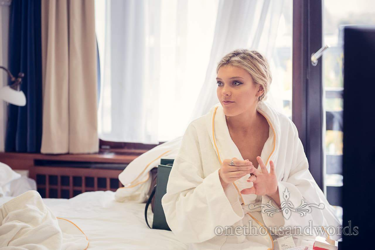 blonde bridesmaid in hotel robe watches wedding morning preparations