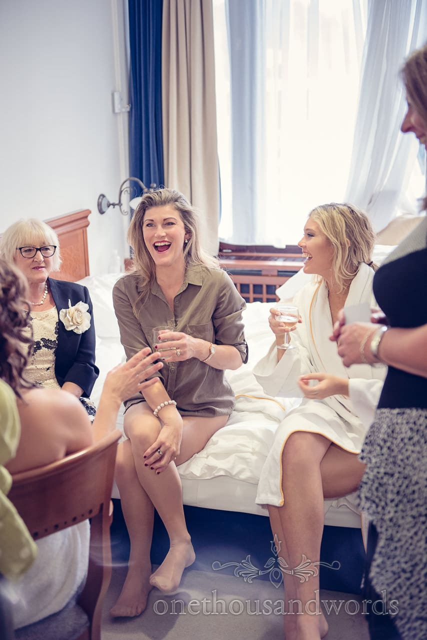Bridal party laughs on hotel bed as bride prepares for wedding day in Bled, Slovenia
