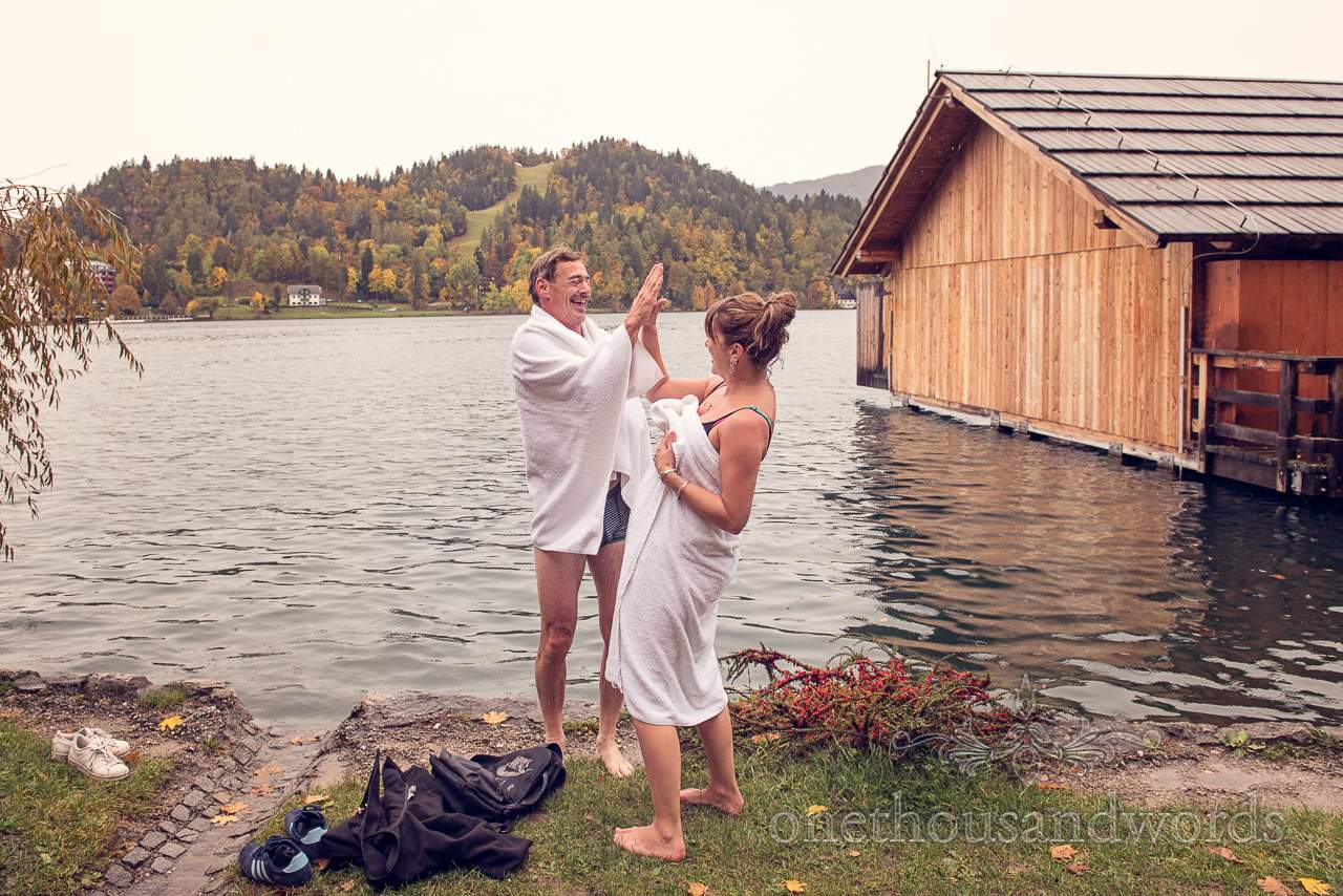 Bride and groom high five after swimming in lake Bled, Slovenia