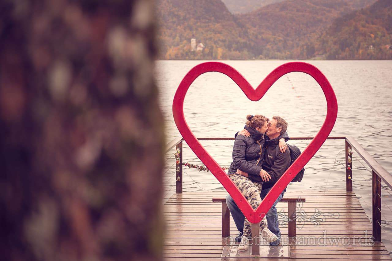 Bride and groom kiss behind giant love heart at Lake Bled, Slovenia