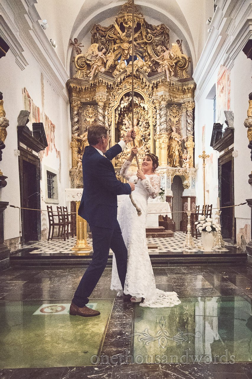 Bride and groom ring wishing bell at Church of the Assumption of Mary, Lake Bled