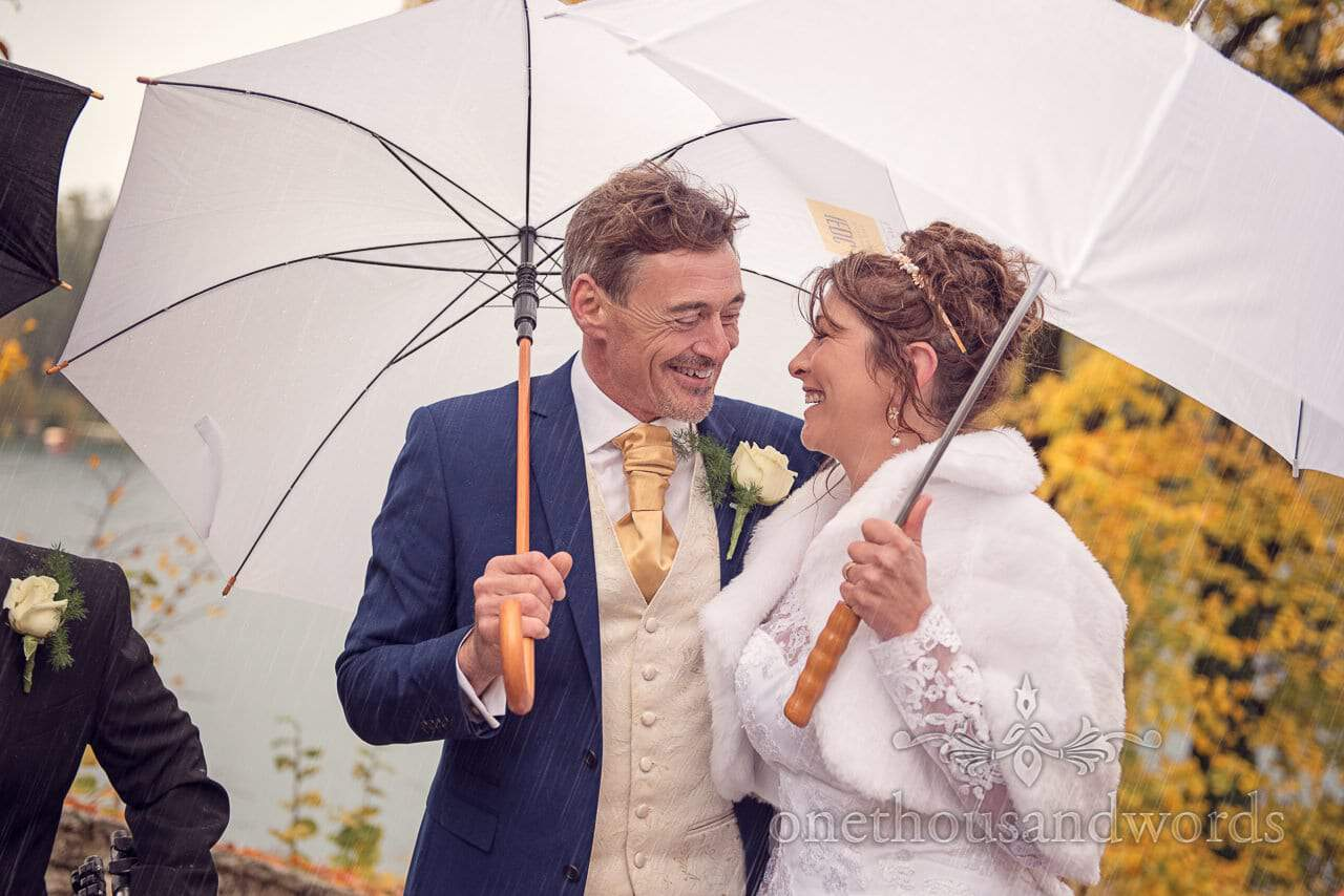 Bride and groom under white umbrellas in the rain on Bled Island, Slovenia