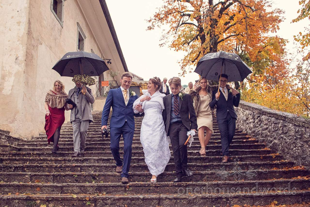 Bride, groom and wedding guests descend the 99 steps on Bled Island, Slovenia