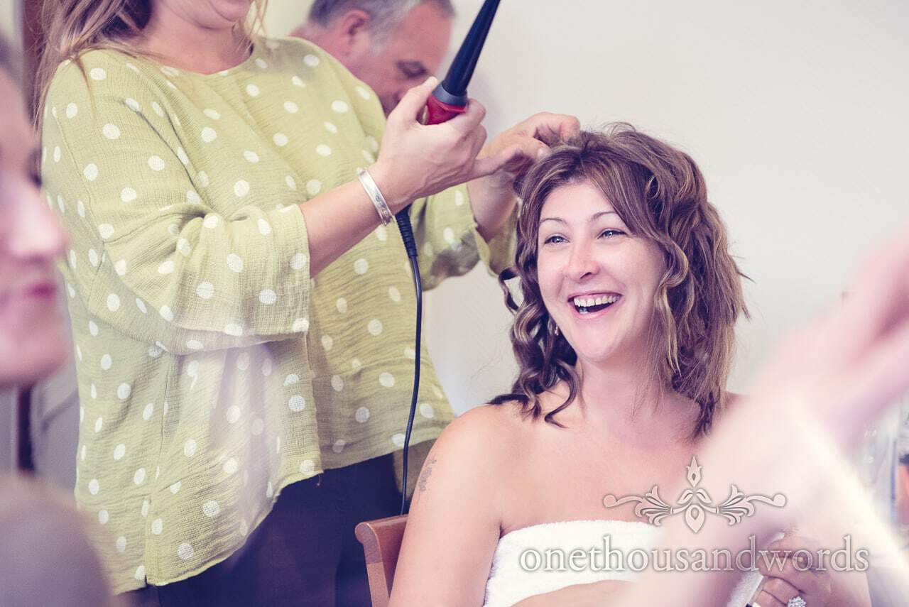 Bride laughs as she has her wedding hair styled on wedding morning in Bled