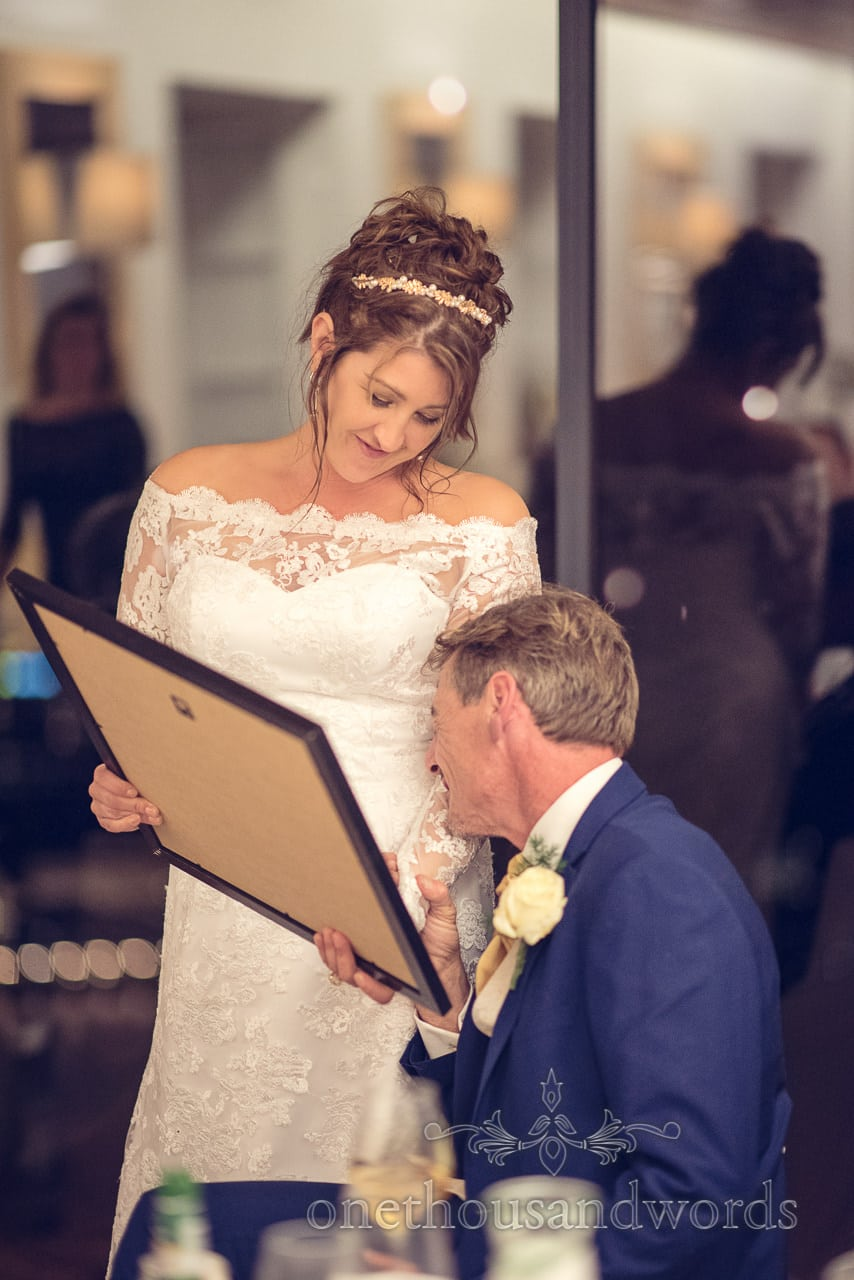 Bride presents groom with emotional photographs in frame at destination wedding