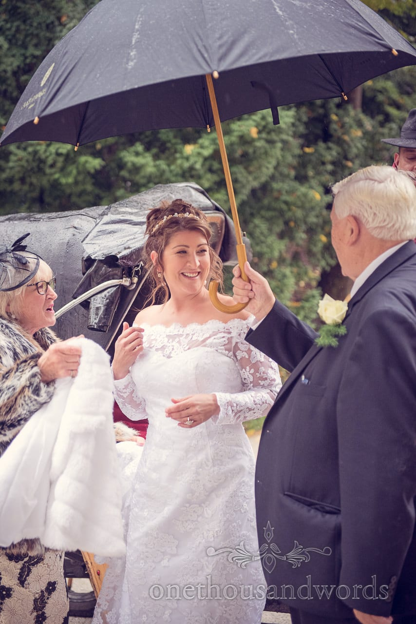 Bride under umbrella in the rain outside Bled Town Hall Wedding in Slovenia