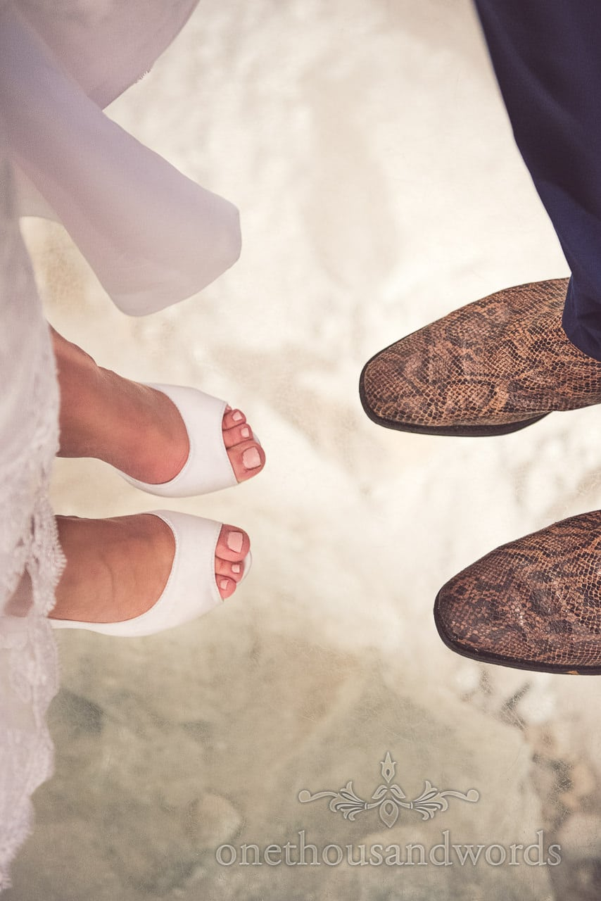 Bride's white wedding shoes and grooms snake skin boots on glass floor