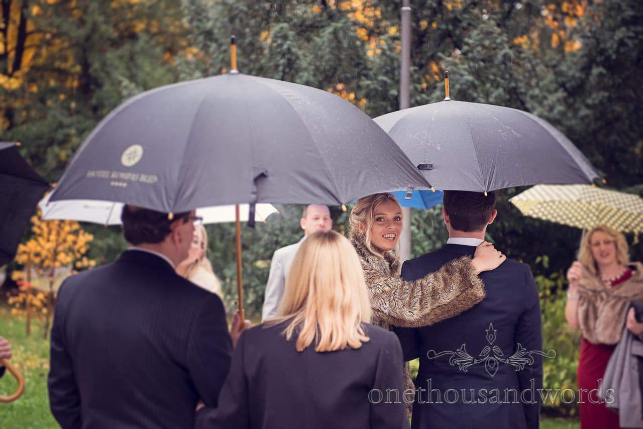 Bridesmaid in fur looks back under wedding umbrellas outside Bled Town Hall wedding