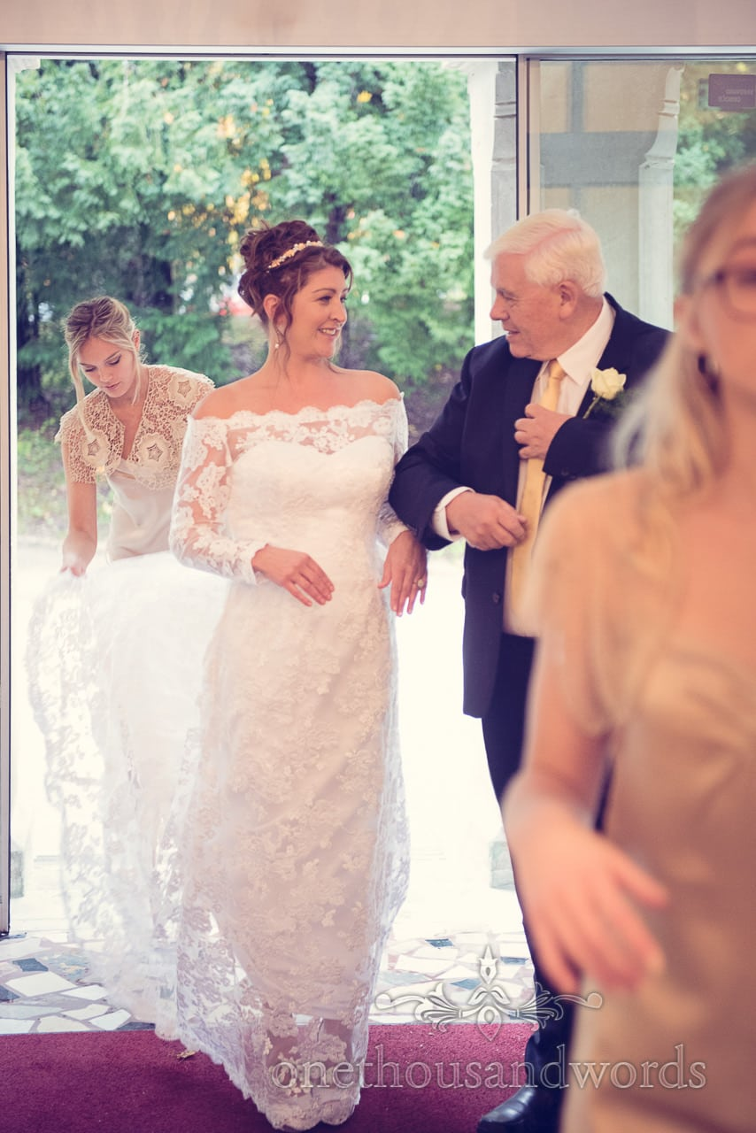 Bridesmaid in gold helps bride as she enters her Slovenian wedding ceremony